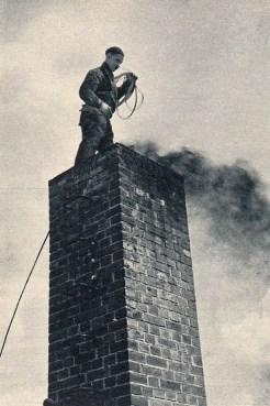 sw-Foto: Kaminfeger steht über dem rußenden Schornstein