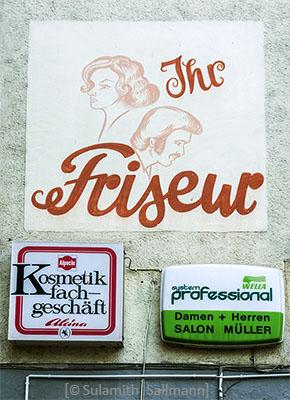 Farbfoto: Wandbemalung mit schön frisiertem Damen- und Herrenkopf