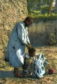 kolorierte AK: am Boden im Freien sitzender Mann wird von stehendem Friseur bearbeitet