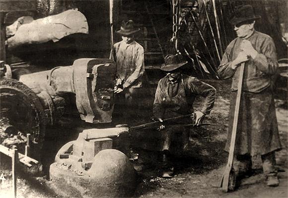 sw Foto: neben Schmied am Eisenhammer stehen ein junger und ein alter Gehilfe - 1890