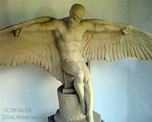 Farbfoto: Skulptur probiert auf Amboss sitzend seine geschmiedeten Flügel an