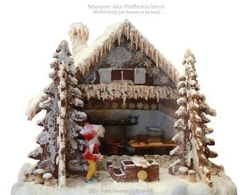 Farbfoto: offenes Pfefferkuchenhaus mit Blick in Miniaturbackstube