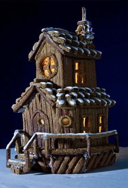 Farbfoto: rustikales zweistöckiges Lebkuchenhaus mit Zuckerguß-Schnee