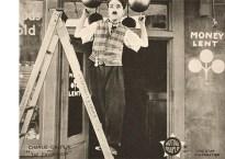 Werbekarte: Charlie Chaplin auf einer Klappleiter