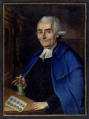 Buchmalerei: Mann sitzt an Tisch mit Knöpfen und hält Quaste in der Hand
