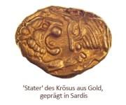 Farbfoto: Goldmünze zeigt Löwe, der frontal einen Stier angreift