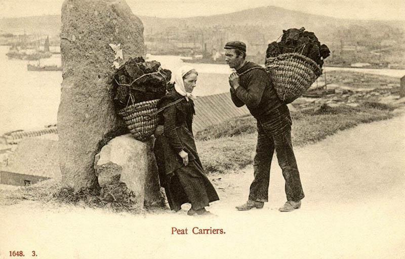 zwei Torfträger mit beladenem Korb auf dem Rücken - Frau und Mann