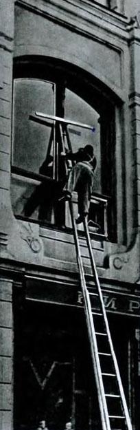 sw-Foto: Fensterputzer auf sehr hoher Leiter beim putzen einer Scheibe