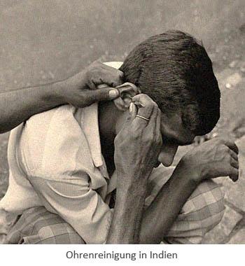 sw Ak-Fotoausschnitt: am Boden hockender Inder lässt sich Ohren reinigen
