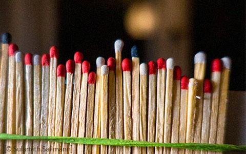 Farbfoto: aufgereihte Streichölzer im Dunklen