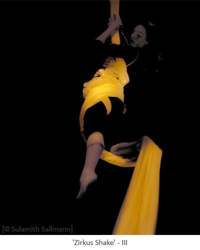 Farbfoto: in gelbleuchtendes Tuch eingedreht aufrecht hängende Tuchakrobatin - 2010, Berlin