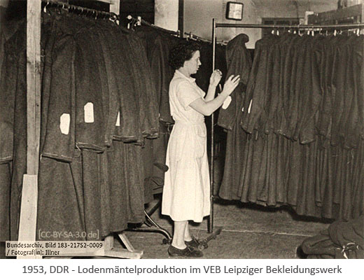 sw Foto: Frau hantiert mit Lodenmänteln auf Kleiderständer - 1953, Leipzig