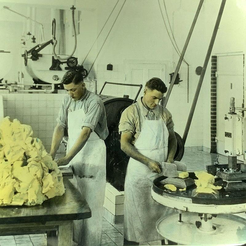 koloriertes Foo: zwei junge Männer packen Butter ab