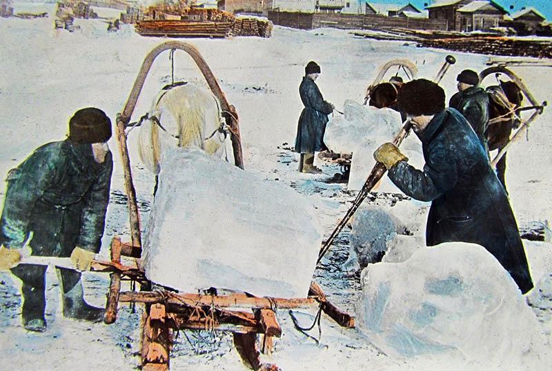 Männer hieven große Eisblöcke auf Pferdeschlitten
