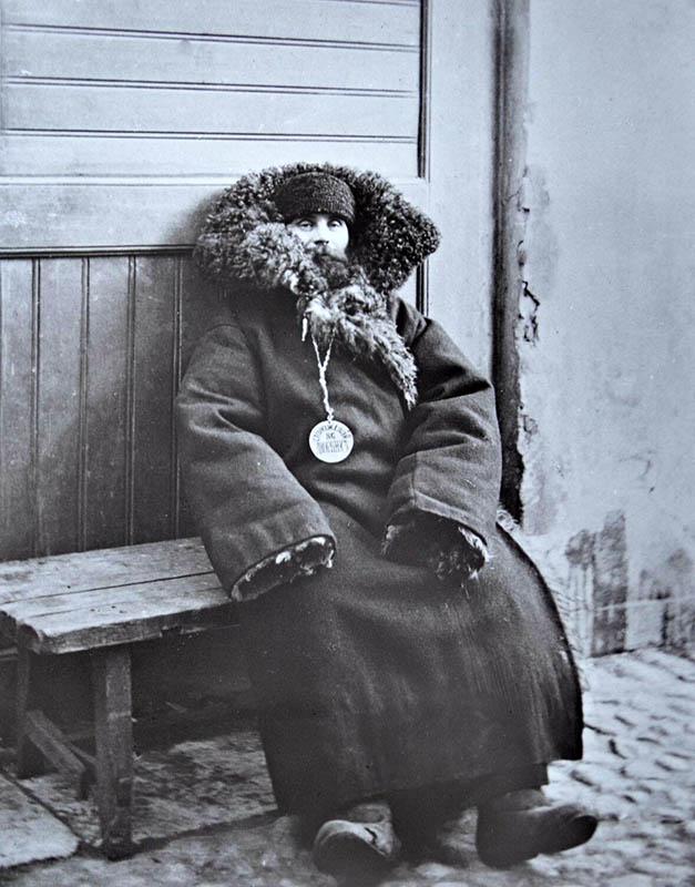 altes Glasdia: Mann in sehr dicken Mantel eingehüllt