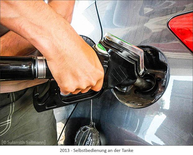 Farbfoto: Nahaufnahme vom Befüllen eines Autotanks mittels Zapfstutzen - 2013