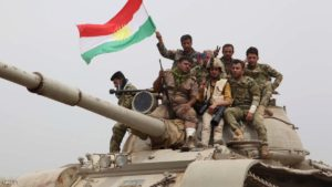 Kurdish Peshmerga fighters sit on top of a tank waving the Kurdish flag on the front line some 35 kilometres south of Kirkuk after they recaptured the northern Iraqi town of Bashir from the Islamic State (IS) group on May 1, 2016.   / AFP / Marwan IBRAHIM        (Photo credit should read MARWAN IBRAHIM/AFP/Getty Images)