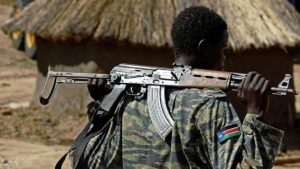 TOPSHOT - A Sudan People's Liberation Army (SPLA) soldier holds a gun at a containment site outside Juba on April 14, 2016. The soldiers at the site are the Tiger Battalion of the presidential guard consisting of a total of 700 soldiers. The site is about 30 km outside of Juba as per the transitional security arrangements of the South Sudan peace agreement. The demilitarisation of Juba is an important part of the peace agreement of the cessation of hostilities signed in August 2015 and seen as a way forward to forming the transitional government of national unity. This has also been a sticking point before the return of Rebel leader Riek Machar who is due to be sworn in as the country's Vice President. / AFP / cds / SAMIR BOL        (Photo credit should read SAMIR BOL/AFP/Getty Images)