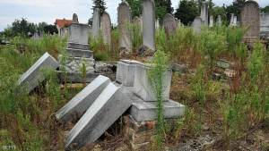 Several broken gravestones lay on the grass on July 22, 2012 in the local Jewish cemetery of Kaposvar, about 200 km south-west from Budapest as fifty-seven graves were desecrated  by vandals. AFP PHOTO/str        (Photo credit should read STR/AFP/GettyImages)