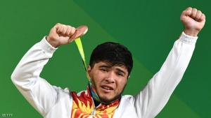 """(FILES) Picture taken on August 9,2016 shows Kirghyzstan's Izzat Artykov posing with his bronze medal on the podium of the Men's 69kg weightlifting competition at the Rio 2016 Olympic Games in Rio de Janeiro.  Izzat Artykov, who won the bronze medal in the 69kg contest, tested positive for strychnine, """"His medal is forfeited and he is excluded from the Olympic Games,"""" the CAS anti-doping tribunal announced.  / AFP / GOH Chai Hin        (Photo credit should read GOH CHAI HIN/AFP/Getty Images)"""