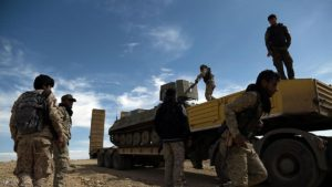 Fighters from the Syrian Democratic Forces (SDF) unload an armoured personnel carrier on the outskirts of the town of al-Shadadi in the northeastern Syrian province of Hasakeh, on February 19, 2016. The Syrian Democratic Forces (SDF), an alliance dominated by the Kurdish People's Protection Units (YPG), seized on Friday the town of al-Shadadi, a bastion of the Islamic State group (IS) in the Hasakeh province, in northeastern Syria, according to the Syrian Observatory for Human Rights. / AFP / Delil souleiman        (Photo credit should read DELIL SOULEIMAN/AFP/Getty Images)