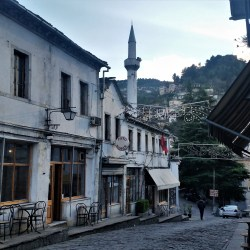 Gyrokaster, Albania – March 25, 2016: Picturesque street and a Mosque minaret at sunset in Gyrokaster, Albania.
