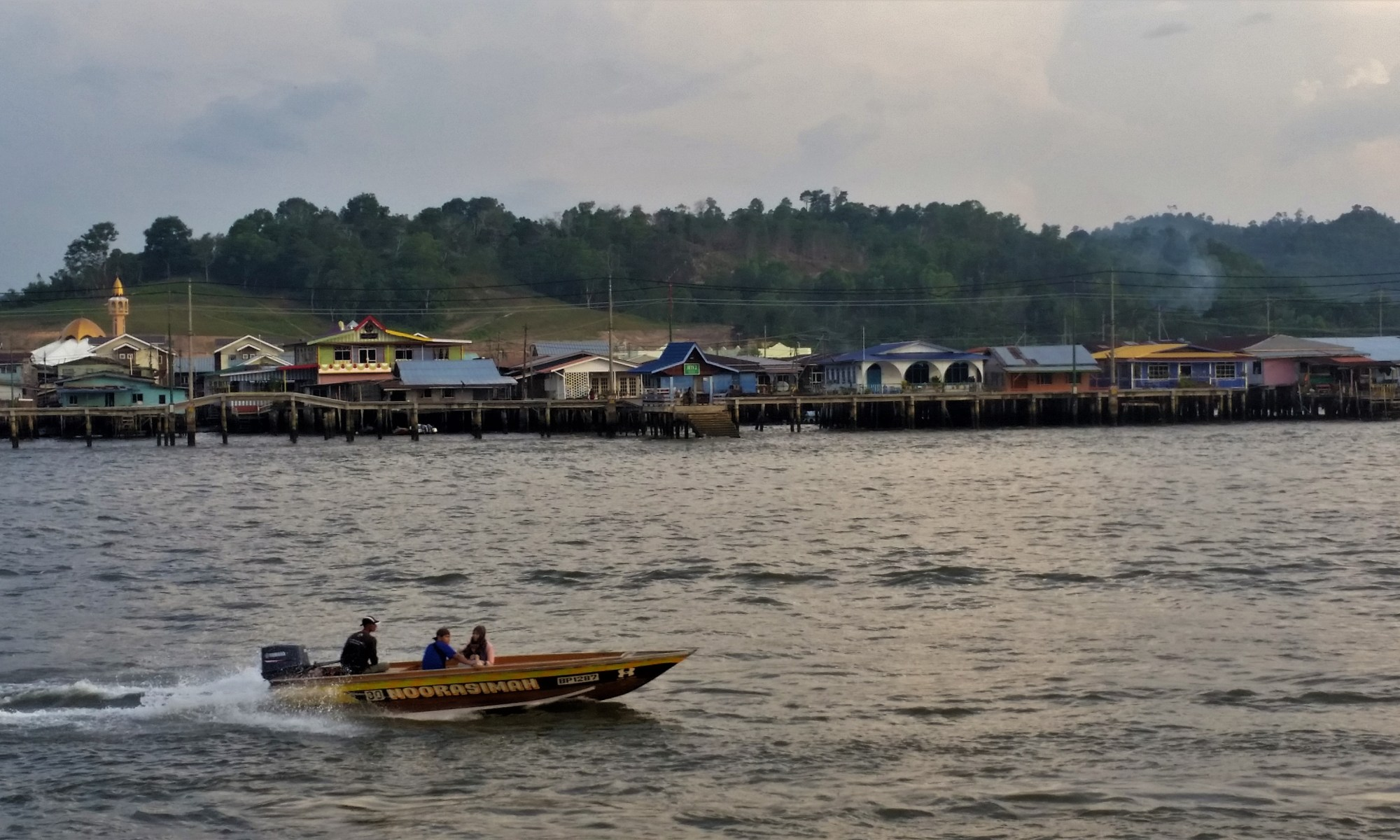 Kampong Ayer, Brunei – July 17, 2015: A motorboat passes by on the water in front of Kampong Ayer, a historic settlement area in Bandar Seri Begawan made of a cluster of traditional stilt villages built on the Brunei River.