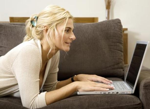 Woman with laptop on sofa