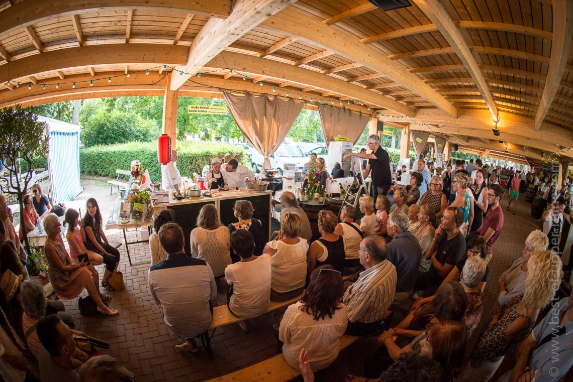 Well sheltered under the beautiful wooden gallery, the chefs make their show in front of a numerous and intrigued audience ...