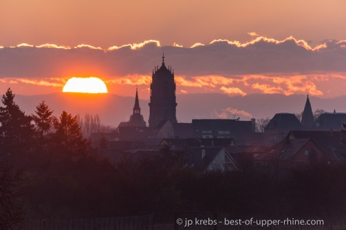 Medieval churches in Selestat and sunrise over the Black Forest in the far.