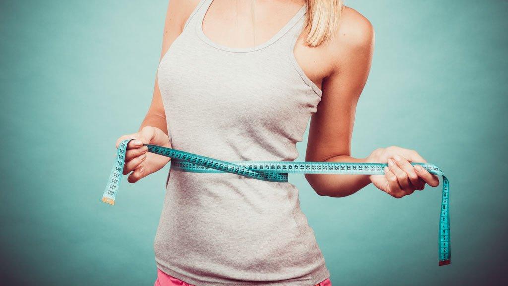 Gewichtsabnahme, schlanker Körper, gesundes Lifestyle-Konzept. Fitnessgirl beim Messen der Taille mit Maßband auf Blau