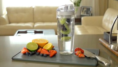the best water bottle for daily use stading on a cutting board with fruits