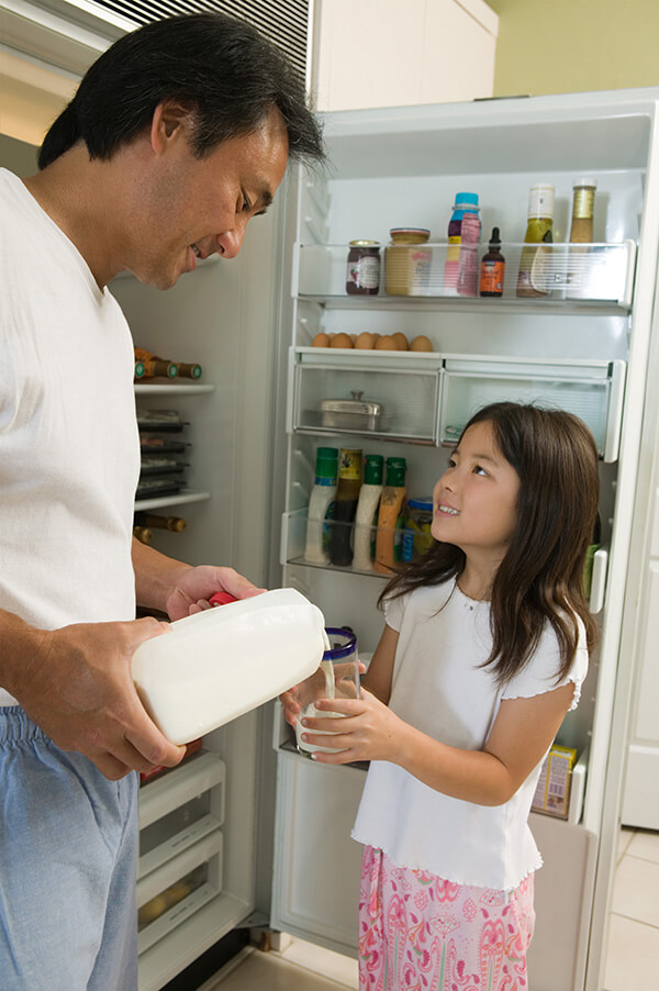 Father pouring milk for daughter by fridge in kitchen