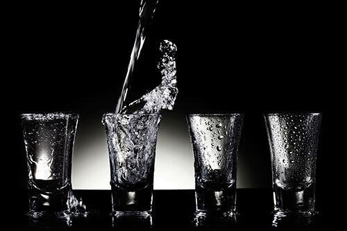 Water pouring into shot glasses