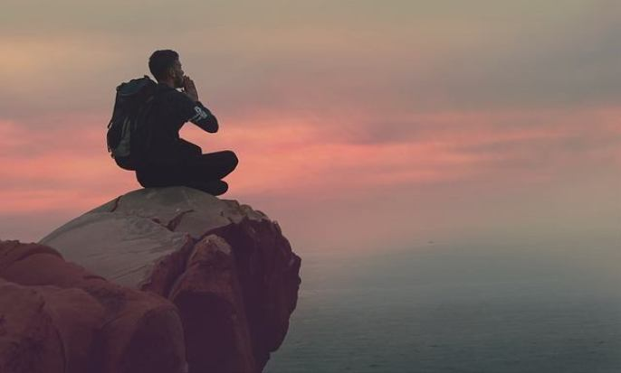 man with backpack sitting on a mountain