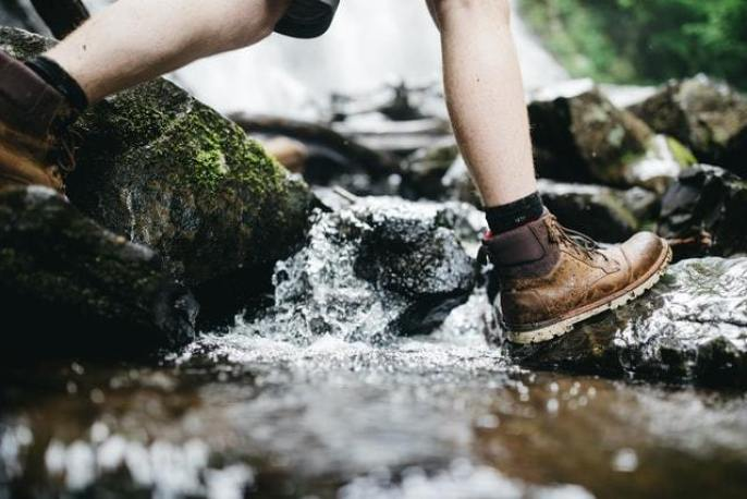 person walking through stream wearing boots