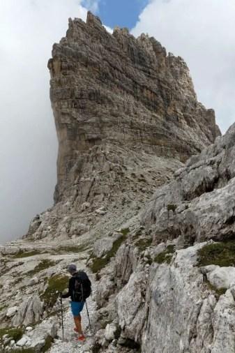 hiker climbing a mountain with trekking poles