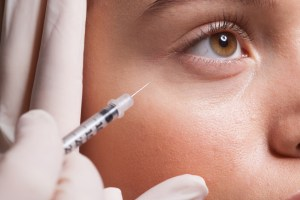 Close up of woman receiving injection under eye to combat frown lines and wrinkles.