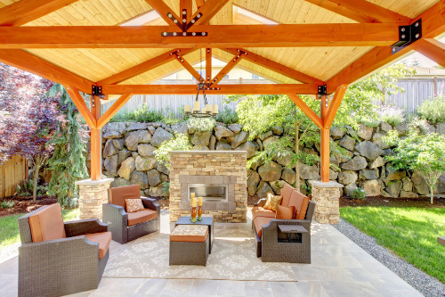 Wooden patio cover with furnishings underneath and stone wall behind them