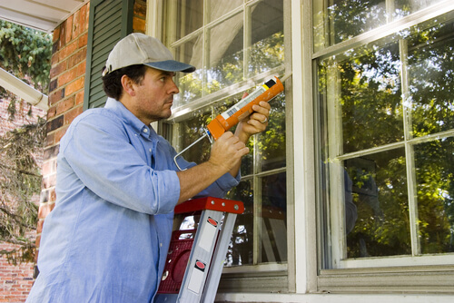 Man repairing roof by putting glue on outside