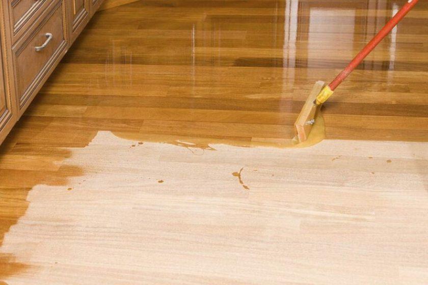 Applying polyurethane varnish in hardwood floor with long handle applicator