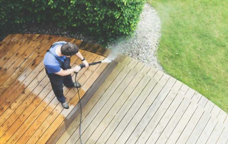 Man cleaning terrace with a power-washer & mold cleaner for wood