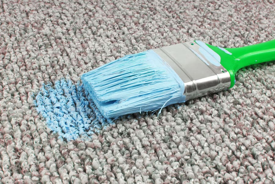 Stained carpet with blue paint on paint brush