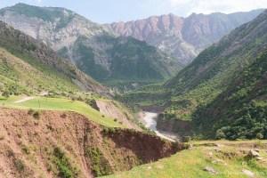 Een wilde rivier stroomt door een diepe kloof tussen de rode en bruine bergen. De vallei is oogverblindend groen