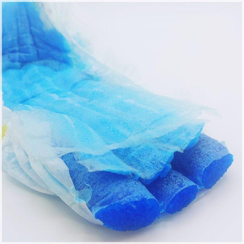Aufbau der Pampers baby-dry Größe 8, oberste Trockenlage, Zwischenvlies mit dicken Zellstoffbahnen und Saugkörper