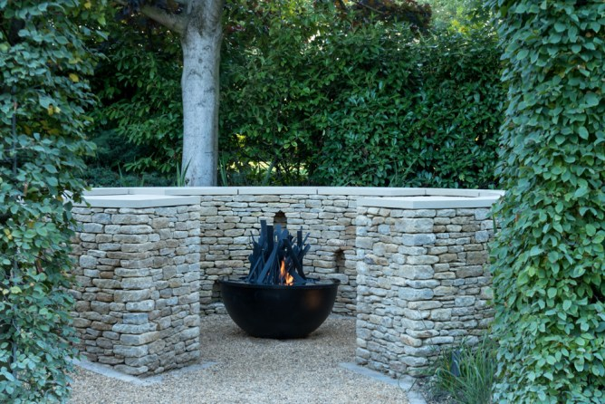 A stone seating area with a gas fire and fire sculpture by Cathy Azria.