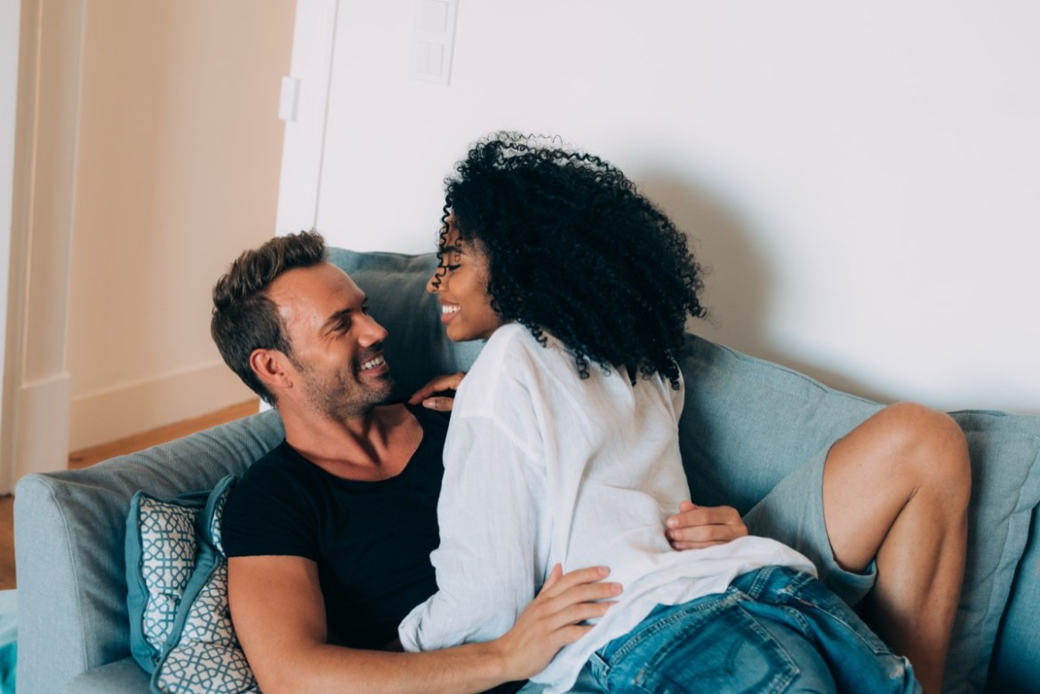 Multiracial couple cuddling on couch