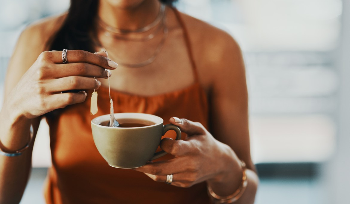 A closeup of a woman steeping a teabag in a cup of tea