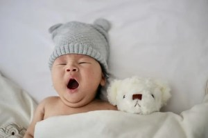 Baby yawning in bed next to a stuffed dog.