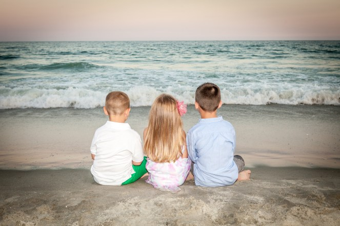 Children sitting on the beach with backs toward photographer at sunset.